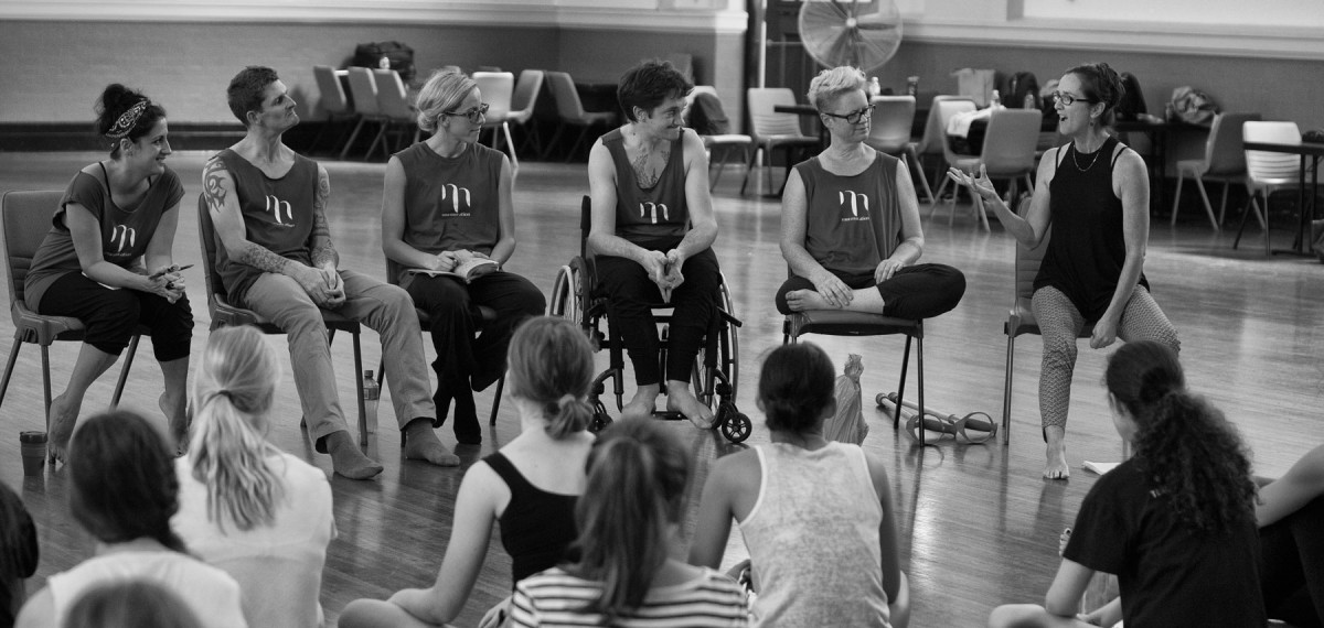 Murmur artists sitting in a row on chairs, alongside Sue Healey, mid discussion, students sitting on the floor in front of them listening intently