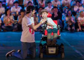 A YA holds microphone up to a young performing who is a wheel chair user. The performer has a big and excited smile on his face, there is a large crowd applauding in the background.