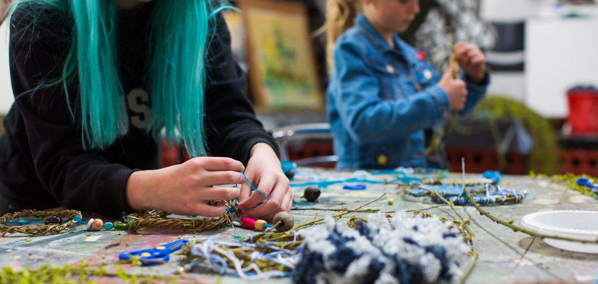 Colour image of two young girls craft making at a workshop bench covered in wool, string, beads and vine.