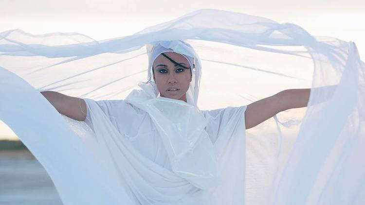 elle Looking at camera wearing a white flowing gown that wraps around her head. It is being lifted by the wind ( Colour Photo)