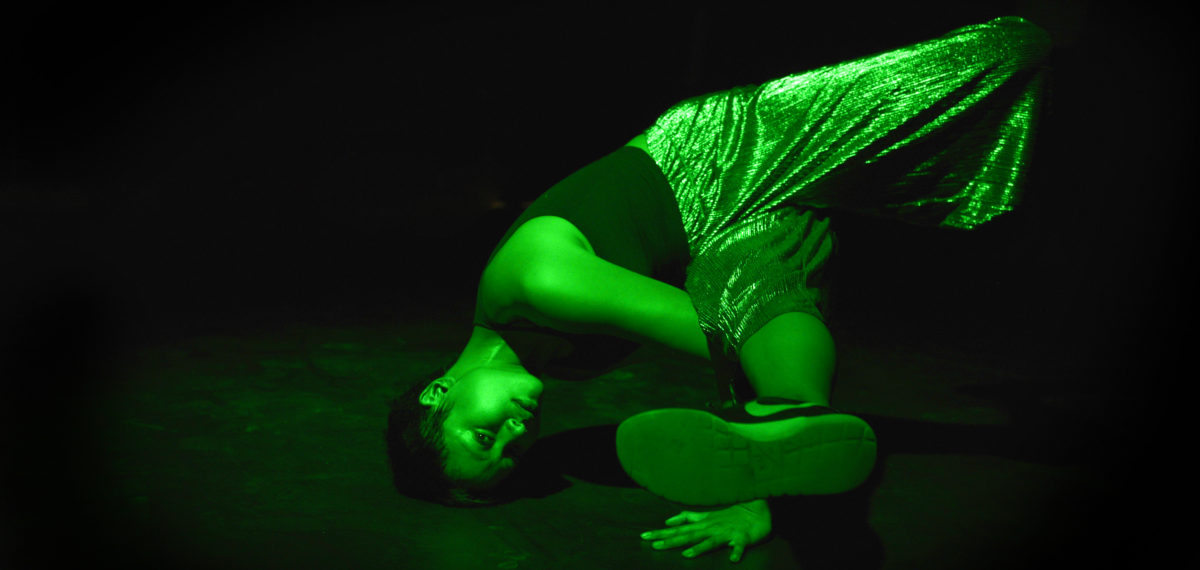 elle Doing a Head Stand in street cloths with a green lighting state on stage. (colour Photo)