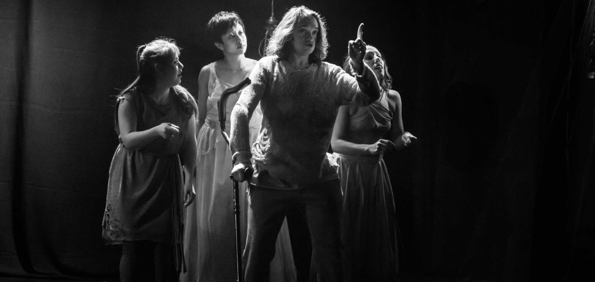 4 performers in wide shot. Man infront of 3 women all facing forward. man using a cane pointing up. (image in Black and White)