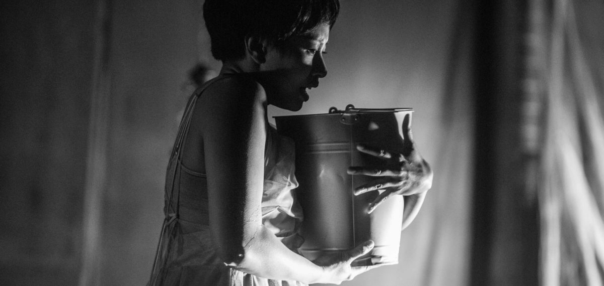 Mid shot of performer in profile holding a metal bucket in both hands close to her chest looking into it (image in black and white)