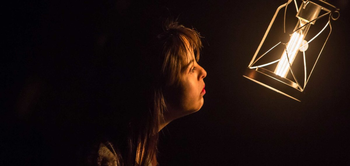 Mid shot of a young women in profile gazing into a hanging lantern, the room is black around her and her face is lit by the orange glow of the lantern.