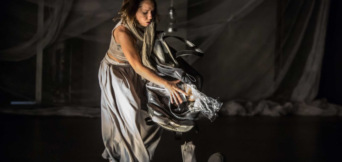 Performer in full body shot. wearing grey dress holding a bag that is falling open (image in colour)