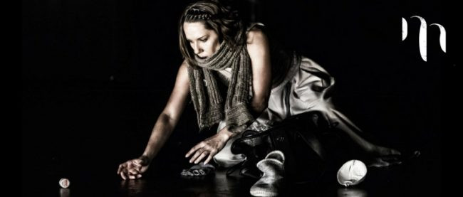 Colour image female performer kneeling in grey outfit with arm outstretched picking small objects off the ground against black background.