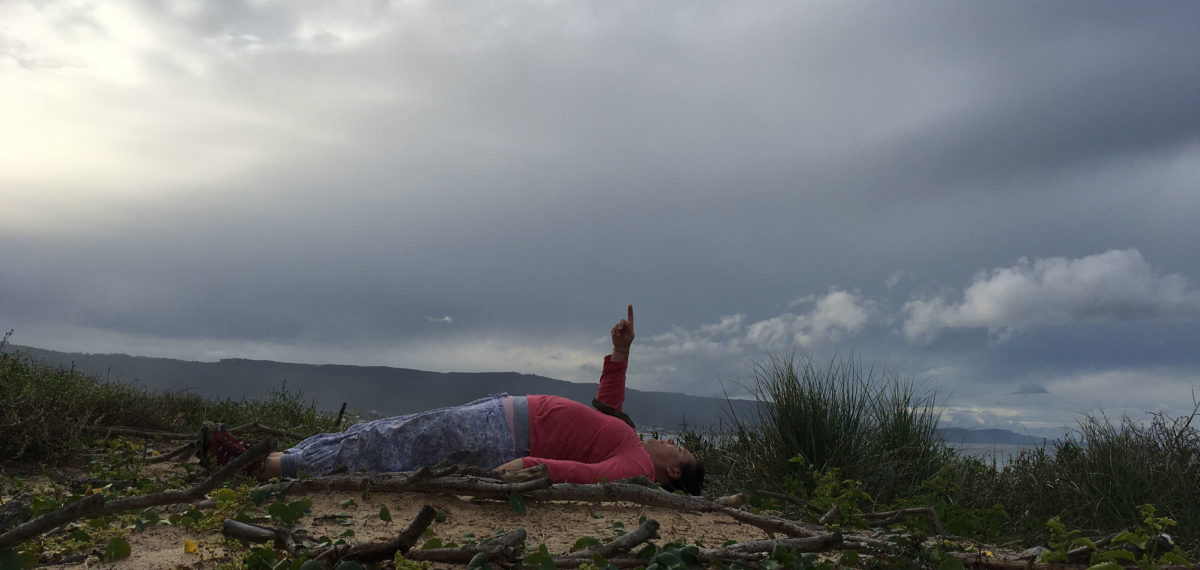 Colour image of woman wearing red shirt and light-blue pants lying on her back on a sandy mound with sticks pointing up to the an expansive cloudy grey sky.