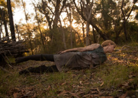 Woman lying stiffly on her side on the ground in bush with sunbeams streaming through trees in the background.