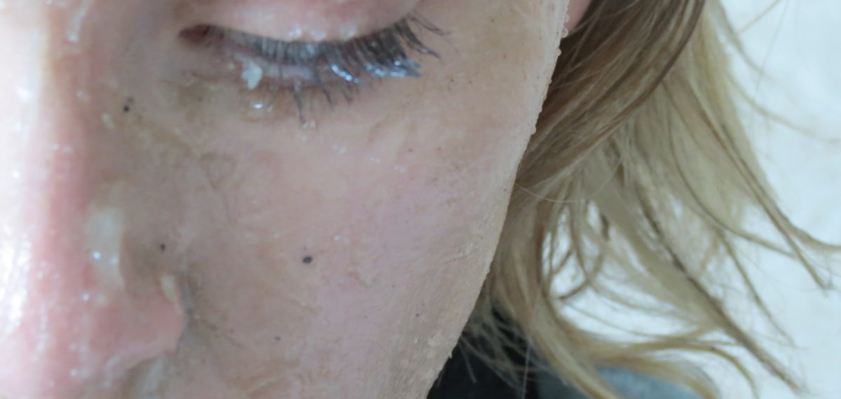 Close up of woman's half opened eye, nose and mouth covered in sand and Vaseline with wispy blonde hair and blue-grey cloth.