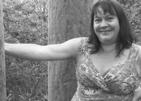 Black and white torso shot of woman with an arm on her hip and the other outstretched and holding a tree in the bush.