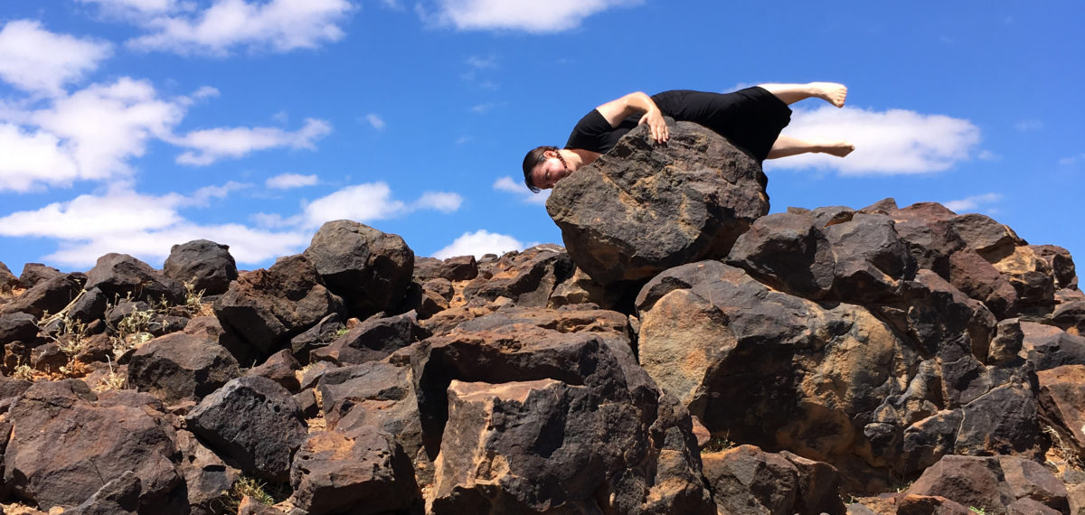 Coloured image with iron stone rocks in foreground and large rock on horizon with artist holding on to it horizontally with legs outstretched against a bright blue sky.