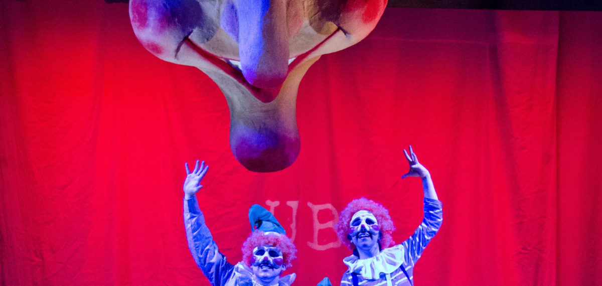 Colour image of red curtained stage with three costumed clowns standing under a large sculptured smiling head prop hanging from the ceiling.