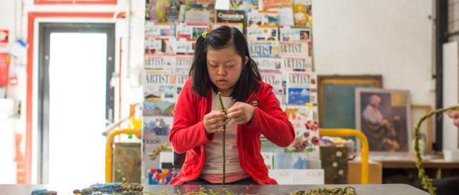 Colour image of a young girl wearing a red jumper creating work with green vine in an art studio. There is a large stand behind her with rows of art magazines.
