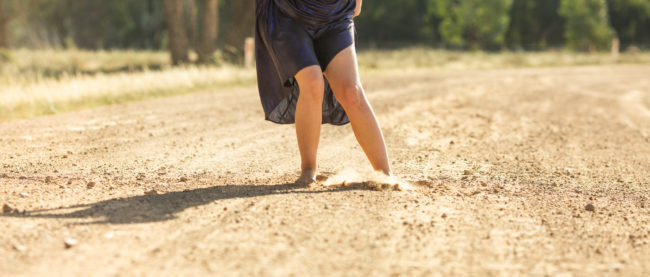 A women is on a dirt road wearing a metallic blue dress, she is leaning forward in motion, we see her bare feet and legs in the dirt as she is pulling up her dress above her knees.-27WEB.jpg
